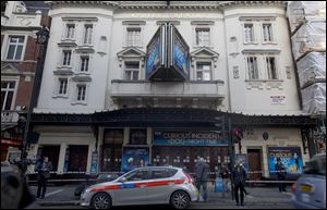 Police stand outside The Apollo Theatre in London, Friday. Authorities are carrying out a structural assessment at the Apollo Theatre after the partial collapse of its ceiling.