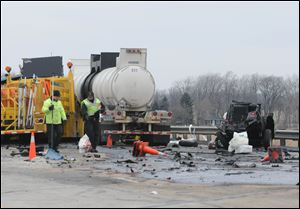 Emergency personnel investigate the scene of a fatal accident on the Ohio Turnpike north of Fremont on Jan 24, 2012. The State Highway Patrol says a tractor-trailer veered into a work zone on the turnpike, killing one worker and seriously injuring two others and the truck driver.