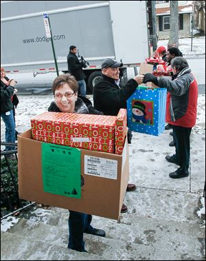 Volunteers unload a truck of holiday presents for  children at Family House in Toledo.