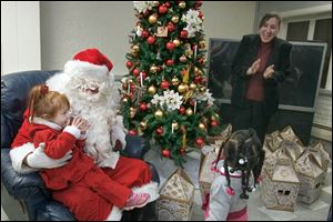 Isabella Mason, 3, talks with Santa Claus while Family House Executive Director Reneé Palacios and Breelyn Jeffers, 2, look on. Chrysler's Toledo Machining Plant employees recently delivered hundreds of gifts to children at the shelter.