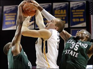 Toledo center Zach Garber (33) battles Cleveland State forward Anton Gady (15) and forward Jon Harris for the ball during the second half.