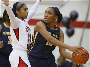 Rogers High School player Marquelle Williams-Price (33) guards Notre Dame Academy player Kaayla McIntyre (15) during the first quarter.