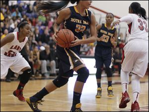 Notre Dame Academy player Jayda Worthy (22) grabs a rebound against Rogers High School during the first quarter.