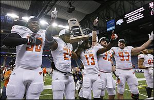 Bowling Green's Izaah Lunsford, left, Jerry Gates, Travis Greene, Paul Swan and Ted Ouellet celebrate a MAC title at Ford Field, where the Falcons will be playing Thursday. BG has sold 7,500 tickets.