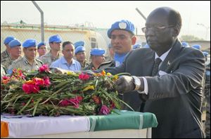 In this photo released by the United Nations Mission in South Sudan (UNMISS), South Sudan's Minister of Foreign Affairs and International Cooperation Dr. Barnaba Marial Benjamin lays flowers on the coffins of the two Indian peacekeepers who were killed on Thursday, at a memorial service held in the UNMISS compound in Juba, South Sudan, Saturday, Dec. 21, 2013.