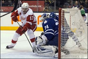 Detroit Red Wings' Pavel Datsyuk, left, scores on Toronto Maple Leafs goaltender James Reimer during a game in December.