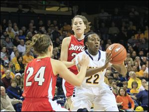 UT's Andola Dortch passes while double teamed by Dayton's Andrea Hoover, right, and Kelley Austria.