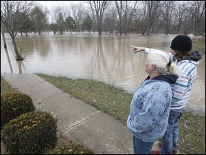 Seth Hocking, right, 13, points out a friend's house that is submerged in flood water to Ellie Silver, left,  on the end of Wilson St. The two do not live in the neighborhood but came out to visit family who live in the area.