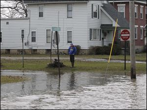 A passerby checks-out the flood water that over took E. Sandusky near downtown.