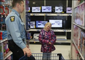 Toledo Police Officer Dan Henderson and Angel Grant, 7, evaluate an item in a toy department. Officers took 53 children shopping for the 12th annual Kids of Christmas program. They met at the Huntington Center downtown and then went to the Meijer store on Alexis Road to shop.