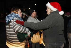 Julie and Keith Thompson are greeted by Toni Harms, right, after receiving food, a blanket, and scarves in the parking lot of Helping Hands of St. Louis. St. John's and St. Ursula students meet every Monday to pass out food to the needy as part of the Labre program.