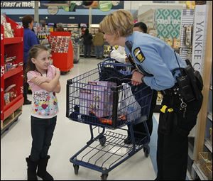 Jayden Salisbury, 7, left, talks with Toledo Police Officer Kelly Jordan. Meijer donated $5,000 to the program and other donors aided as well.