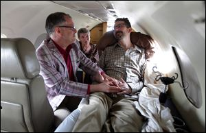 Jim Obergefell, left and John Arthur, right, are married by officiant Paulette Roberts, rear center, in a plane on the tarmac at Baltimore/Washington International Airport in Glen Burnie, Md., in July.
