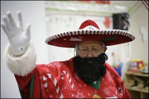 Pancho Claus, Rudy Martinez, waves to children as he visits Knowlton Elementary School, in San Antonio Friday. Pancho Claus, a Tex-Mex Santa borne from the Chicano civil rights movement in the late 1970s and early 1980s, is now an adored Christmas fixture in many Texas cities.