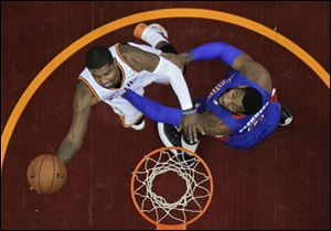 Cleveland Cavaliers' Kyrie Irving, left, shoots against Detroit Pistons' Andre Drummond during the first quarter.