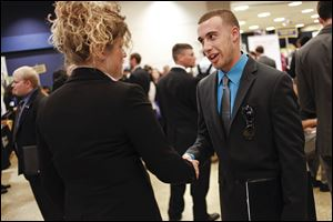 Bradley Campolo shakes hands with Kelsea Kiene of 3M during a University of Toledo job fair in September. More than half of Ohio businesses surveyed said they plan hirings in the first quarter.