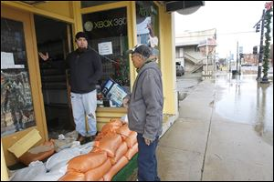 Stephen Scherger, left, owner of Flag City Gaming in Findlay, shows Boun Kantabouth the damage sustained by his store. The sandbags proved futile, but Mr. Scherger said Monday that he was able to save his merchandise.