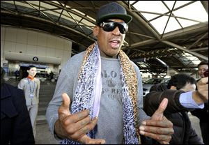 Former basketball star Dennis Rodman speaks to journalists upon arrival at the capital airport in Beijing from Pyongyang, North Korea, today.