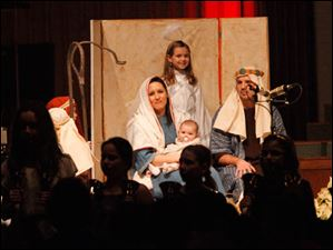 As Kendal Wilson, 9, center, stands over them as the Angel of the Lord, Andrea Swindel, left, holds her daughter, Elise, 5 months-old, while portraying Mary and Jesus, with Eric Swindel, right, as Joseph.