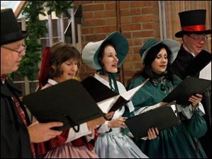 Dickens Carolers Paul Wannemacher, left, Alta Richter, center left, Tess Thompson, center, Robin Campos, center right, and Alan Baker, right, sing carols as church goers head into the sanctuary.