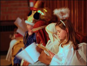 Kendal Wilson, 9, looks at the program while waiting with fellow nativity members.