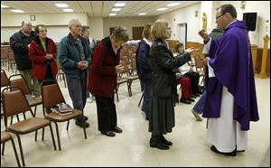 The Rev. Jerry Schetter celebrates mass at St. Barbara Catholic Church's parish hall in Cloverdale, Ohio.  A Nov. 17 tornado destroyed the village's only church.
