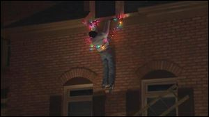 This frame grab from video provided by WSB-TV Atlanta shows an Atlanta homeowner's  Christmas decoration of a mannequin with outstretched arms entangled in a string of Christmas lights and clinging to a ledge.