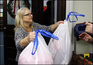 Pam Belew helps distribute bags of toys at the Helping Hands of St. Louis' children's Christmas party. Catholic Charities has been paying her rent  through the Permanent Supportive Housing program.