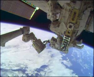 In this image taken from video provided by NASA, astronauts Rick Mastracchio, top, and Michael Hopkins work to repair an external cooling line on the International Space Station today, 260 miles above Earth.