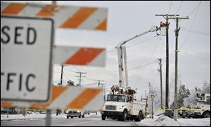 Crews work to restore power lines that were damaged along DeMille Road in Lapeer, Mich. on Monday, Dec. 23, 2013, after the ice storm over the weekend. (AP Photo/Detroit News, Robin Buckson)