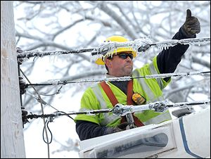 Dave Dora, an employee of a  Grand Haven utility company, gives a thumbs up to a worker as they reconnect fallen wires in Lansing. One utility firm said the wintry blast was the largest Christmas week storm in the company's 126-year history.