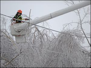 Andrew Powers, an arborist with Asplundh Tree Experts, clears iced branches from power lines along Mayflower Heights Drive in Waterville, Maine, on Monday.