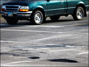 A truck passes through the intersection of North Wheeling and Consul streets in East Toledo. The recent fluctuation in temper-atures has caused potholes in many area streets and roads.