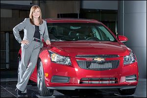 Mary Bara, 52, with a 2011 Chevrolet Cruze, started at General Motors when she was 18 and showed leadership abilities while  later working within the company's team of engineers.
