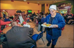Volunteer Shelley Carithers serves a plate to Adam Gross, left, during a Christmas meal at the Cherry Street Mission in Toledo. About 350 dinners were prepared for the event, a tradition at the mission.