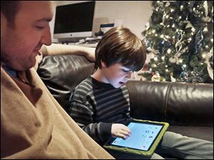 Adam Cohen watches as his son Marc, 5, uses a tablet at their home in New York. Mr. Cohen says apps have been a key part of Marc's education.