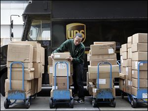 A UPS driver unloads packages from a truck and arranges them for delivery in New York. The company said today that the volume of air packages exceeded its capacity immediately preceding Christmas.