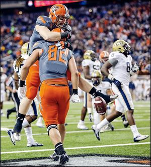 Bowling Green's Alex Bayer is hugged by teammate Tyler Beck after scoring a touchdown against Pitt. Bayer finished with three catches for 57 yards in the loss for the Falcons.