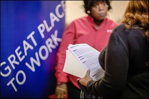 This November, 2013, photo shows a woman with a resumé talking with  a recruiter for Delta airlines at a job fair for veterans and family members  in Marietta, Ga. December's job creation figures were the weakest in three years.