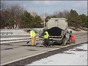 A city crew patches potholes Thursday on the Anthony Wayne Trail near I-75 on the approach to downtown Toledo.