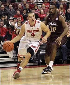 Ohio State's Aaron Craft, left, drives the baseline against Louisiana-Monroe's Amos Olatayo during the first half.