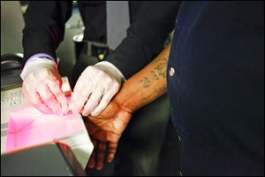 A man brought in by the Toledo police Gangs Unit has his fingerprints scanned by a corrections officer in the booking area of the Lucas County jail. Tattoos are sometimes photographed.