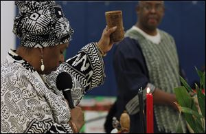 Rolita Noble uses a cup of water for the libation ceremony to honor ancestors, during the annual Kwanzaa celebration at the Frederick Douglass Community Center in Toledo.