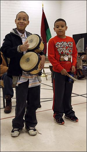 Antonio Moore Oxner, 11, left,  and Tristan Headrick, 7, play instruments as part of the festivities. The cele-bration continues today.
