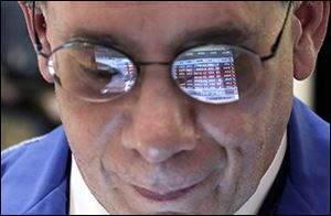 Trader Sal Suarino's glasses reflect numbers on the New York Stock Exchange, where the Dow set a record in March.