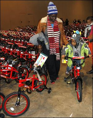 Jaron Smith, 3, tries out his new bicycle as his grandmother, Rachelle Ford, watches.