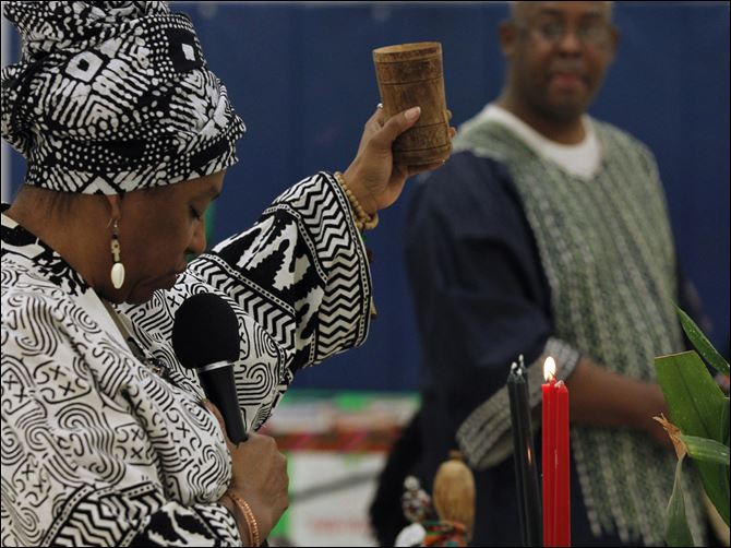 CTY kwanzaa27p Rolita Noble uses a cup of water for the libation ceremony to honor ancestors, during the annual Kwanzaa celebration at the Frederick Douglass Community Center in Toledo.
