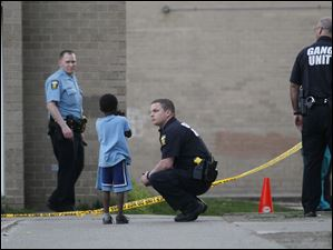 Reuben Jurva, right, with the Toledo Gang Unit speaks to a youngster at the scene of a shooting at the Greenbelt Place apartments where authorities investigated the scene of a shooting on May 1.