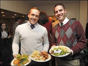Clark Leach, left, and William Kruger with food served at the holiday dinner at the Carranor Hunt and Polo Club in Perrysburg.