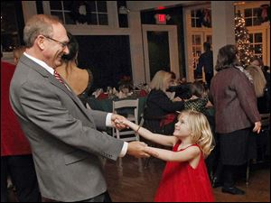 Ray Corrigan dances with granddaughter Claire Wellstein, 5, at the holiday dinner at the Carranor Hunt and Polo Club in Perrysburg.